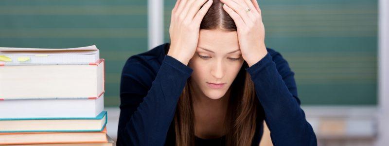 ragazza con mani tra i capelli che non riesce a studiare