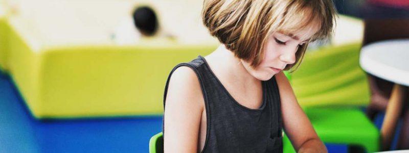 bambini all'asilo nido che scrive seduta al banco
