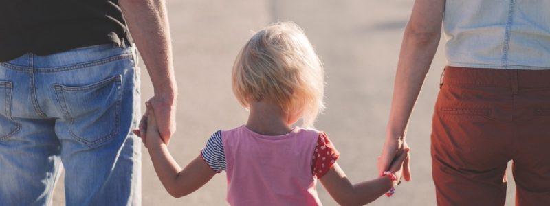 genitori e bambina di spalle mano nella mano