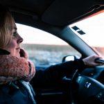 donna al volante guida con espressione preoccupata