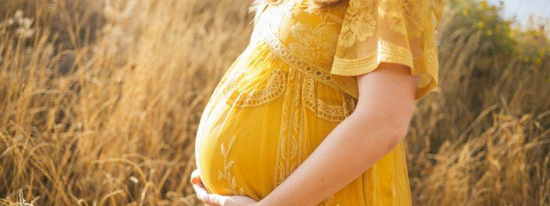 donna incinta con vestito lungo giallo tra spighe di grano si tocca la pancia